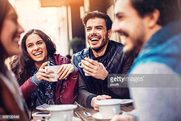 Smiling friends drinking coffee