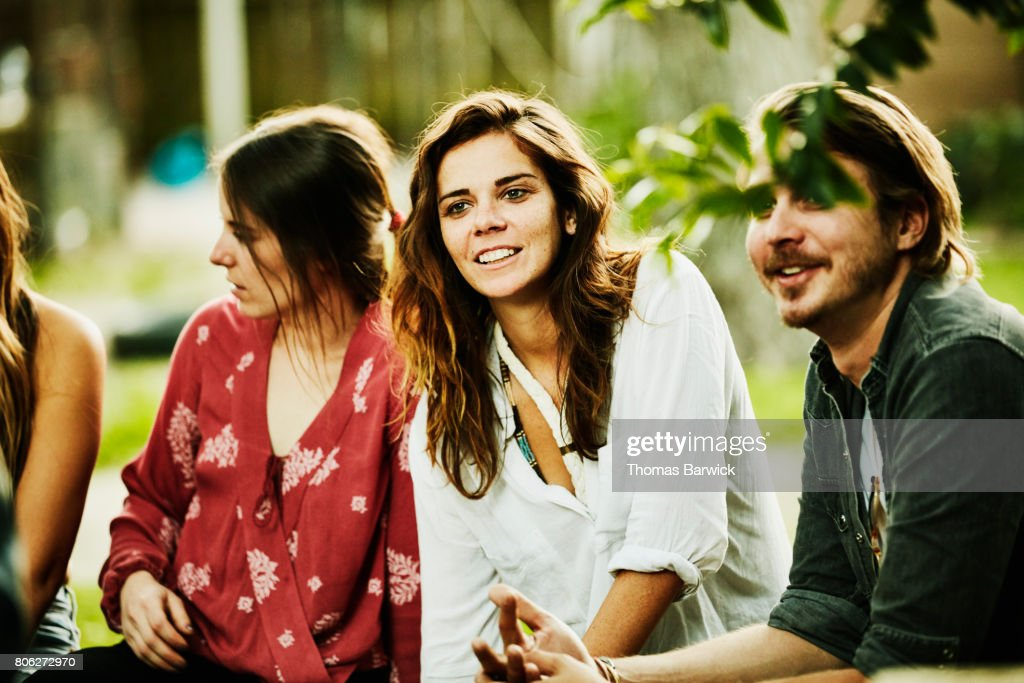 Smiling friends hanging out in backyard on summer evening : Stock Photo