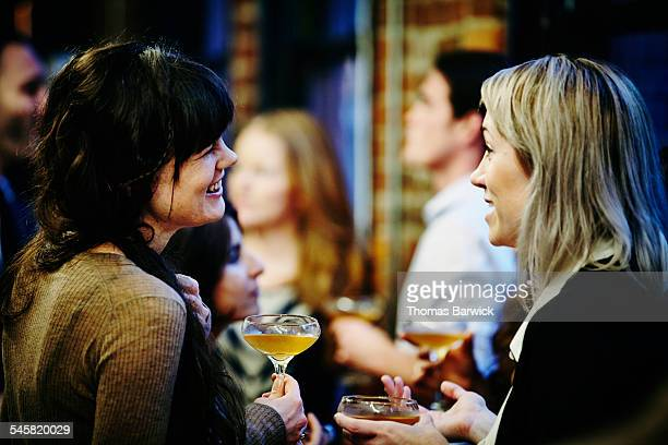 Smiling friends having drinks at dinner party