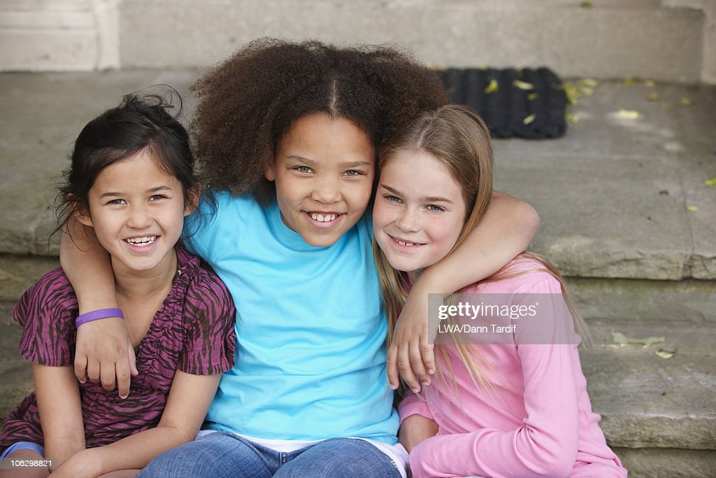 Smiling friends hugging on front stoop : Stock Photo