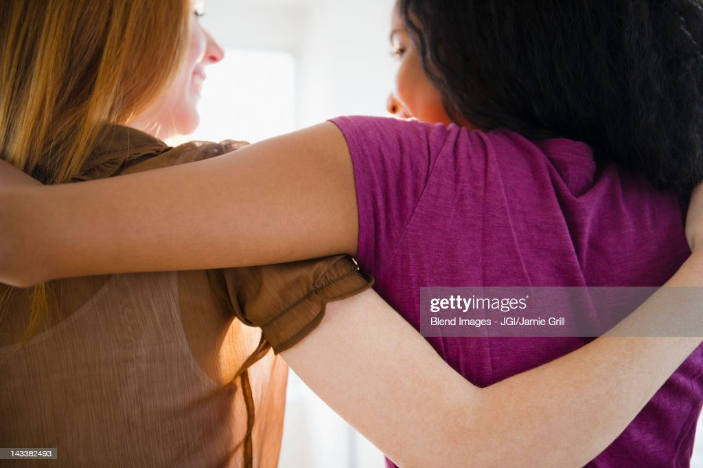 Smiling friends hugging : Stock Photo