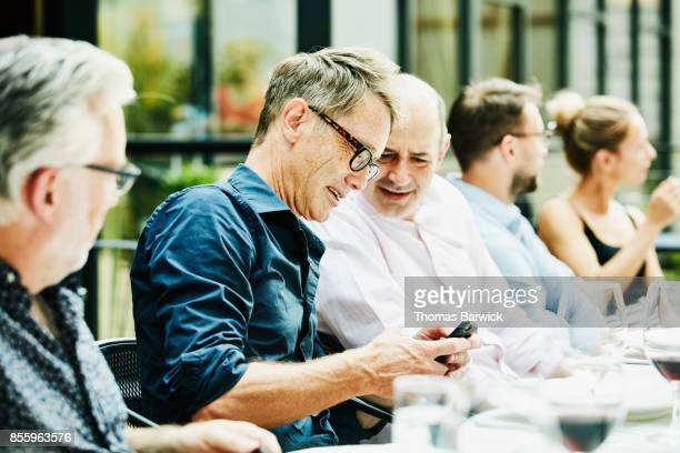 Smiling friends looking at smartphone during dinner on restaurant patio