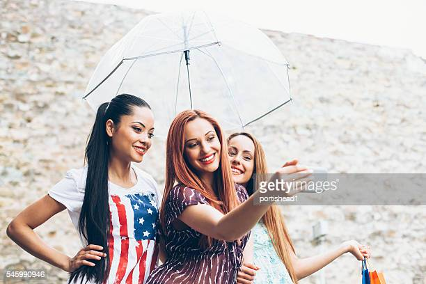 Smiling friends making selfie with umbrella and purchases