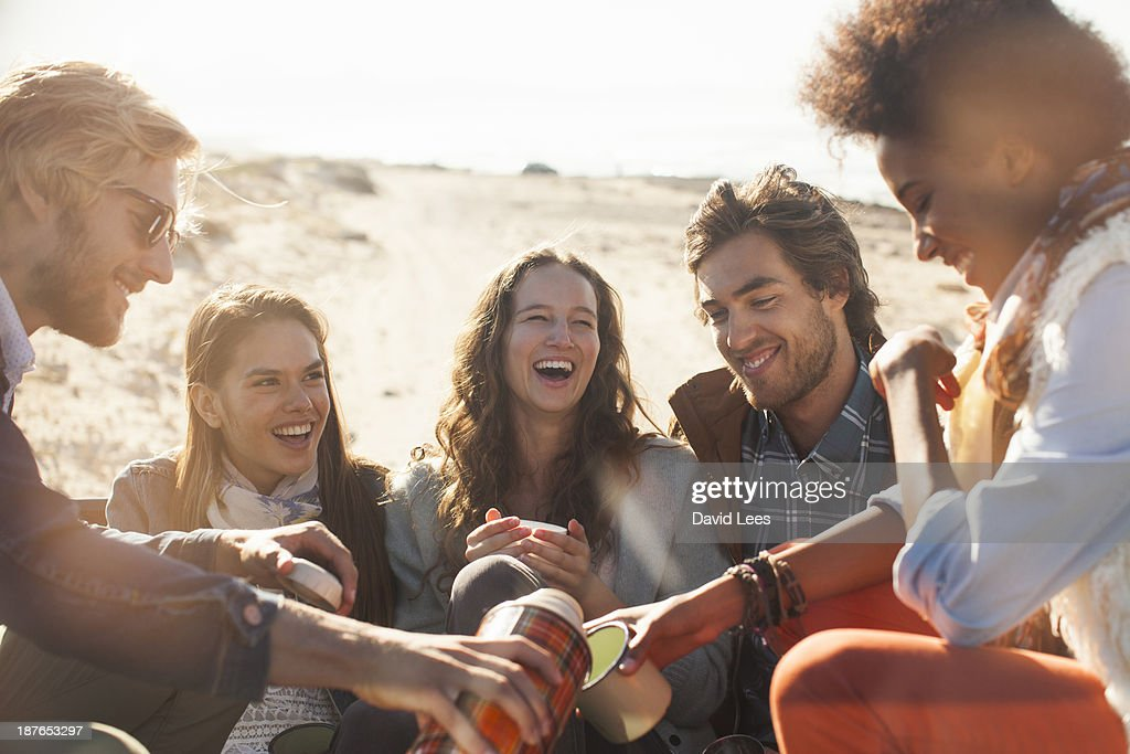 Smiling friends relaxing at beach : Stock Photo