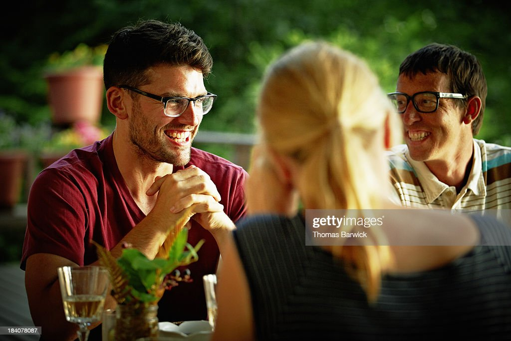 Smiling friends sharing a meal on deck of cabin : Stock Photo