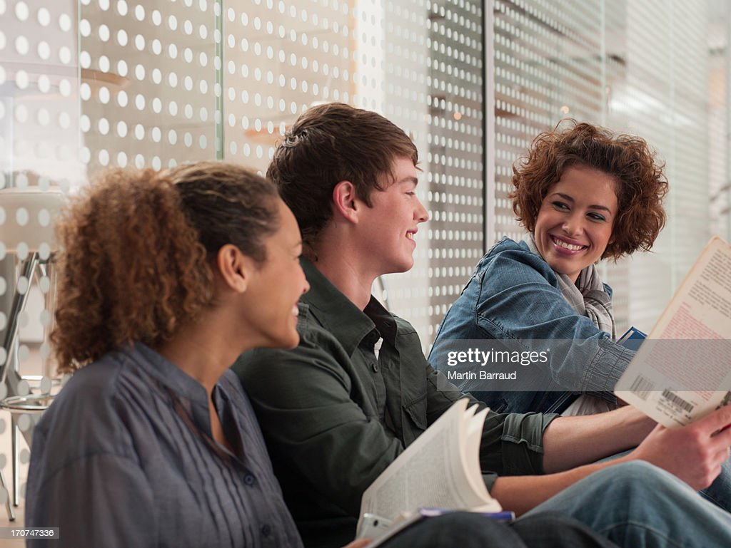 Smiling friends sitting in a row with holding book : Stock Photo