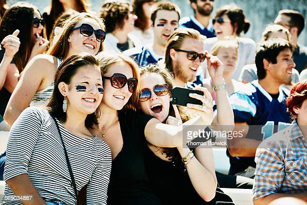 Smiling friends sitting in stadium taking selfie