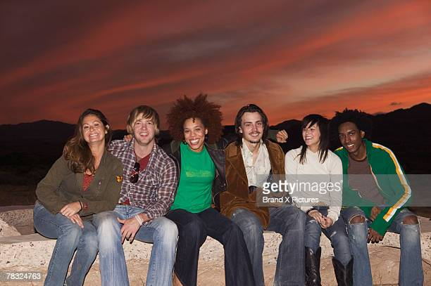 Smiling friends sitting together at sunset