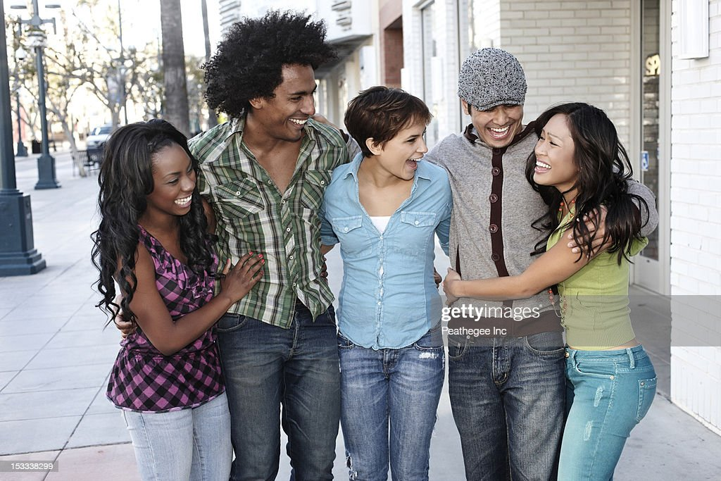 Smiling friends standing together hugging : Stock Photo