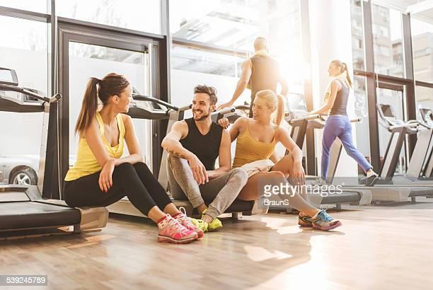 Sonriendo amigos tomando un descanso de ejercicio en el gimnasio.