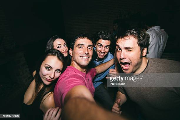 Smiling friends taking selfie in nightclub