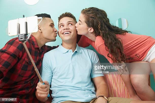 Smiling friends taking selfie kissing cheeks of man