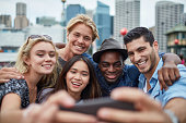 Group of happy multi-ethnic friends taking selfie on smart phone. Young men and women are smiling together. They are wearing casuals in city.