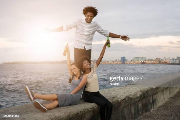 Sourire des amis griller le Malecon, la bière, la Havane, Cuba