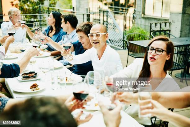 Smiling friends toasting during celebration dinner on restaurant patio