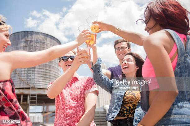Smiling friends toasting with beer outdoors