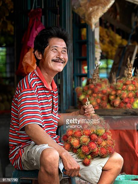 A smiling fruit vendor with rambutans.