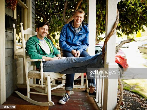 Smiling gay couple seated together on front porch