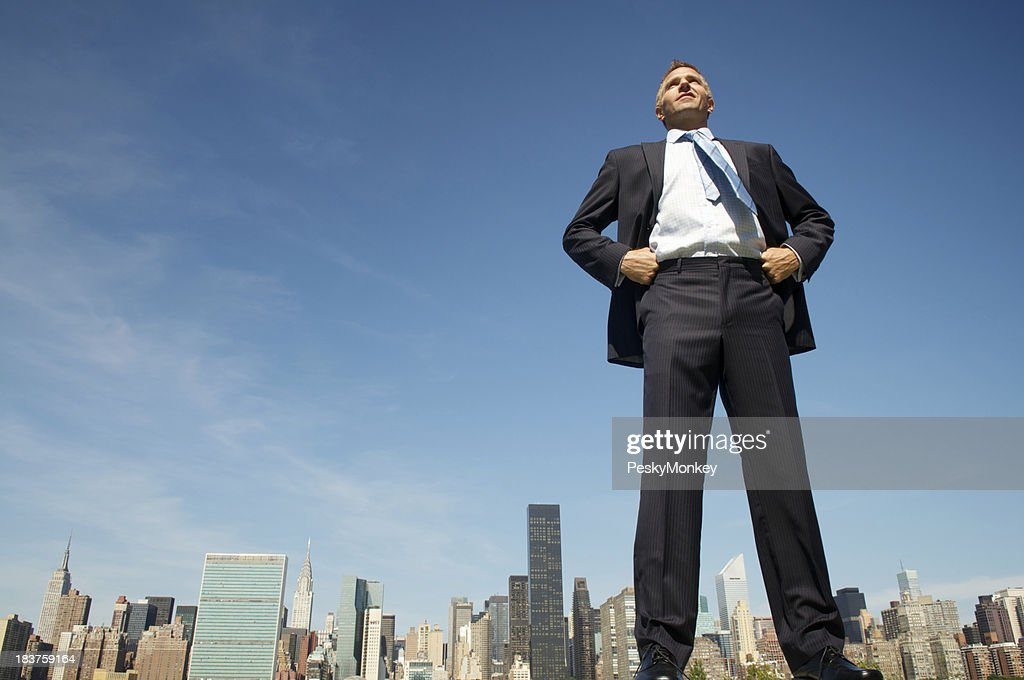 Businessman Stands Tall and Proud Above City Skyline