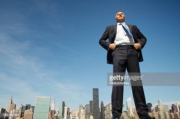 Lächelnd Giant Geschäftsmann stehend groß und stolz über die Skyline der Stadt
