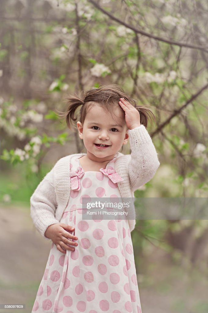 Smiling girl against blossoming tree in spring
