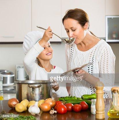 Niña sonriente y madre en cocina : Foto de stock