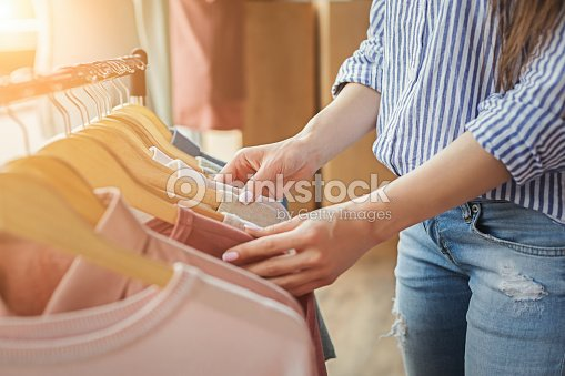 Smiling girl bying clothes in showroom : Stock Photo