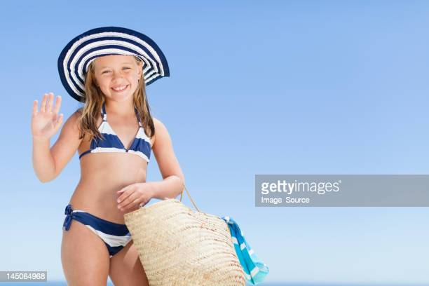 Smiling girl carrying straw bag outdoors