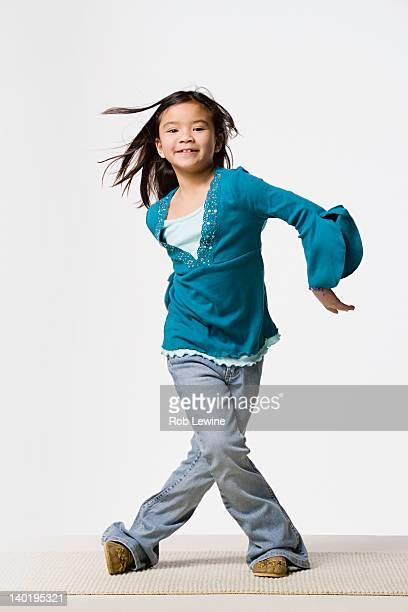 Smiling girl (8-9) dancing, studio shot
