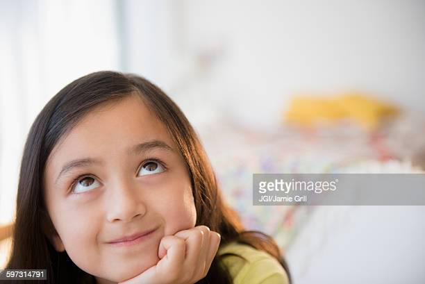 Smiling girl daydreaming with hand on chin