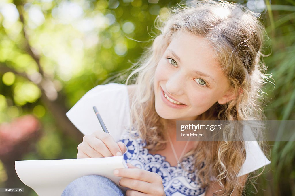 Smiling girl drawing on sketch pad : Stock Photo