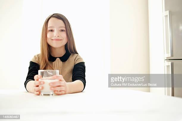Smiling girl drinking milk in kitchen