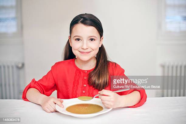 Smiling girl eating bowl of soup