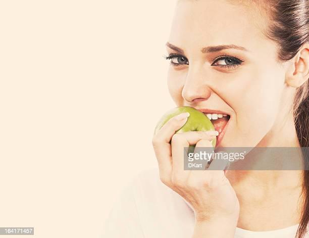 Souriant fille mange une pomme verte