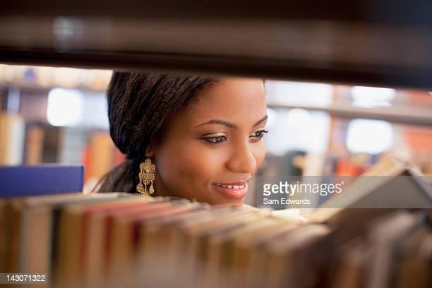 Ragazza sorridente esaminando libro nella Libreria