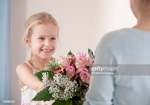 Smiling girl giving mother bunch of flowers