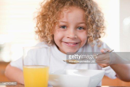 Smiling girl having breakfast in the kitchen : Foto stock