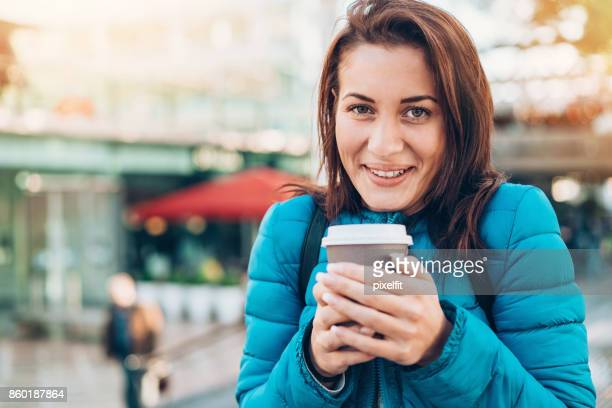 Smiling girl holding a hot drink outside on a cold day