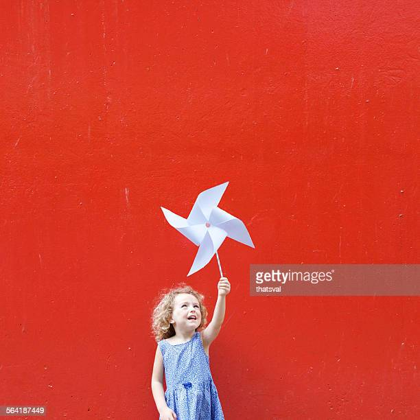 Smiling girl holding a pinwheel in the air making a Hong Kong flag