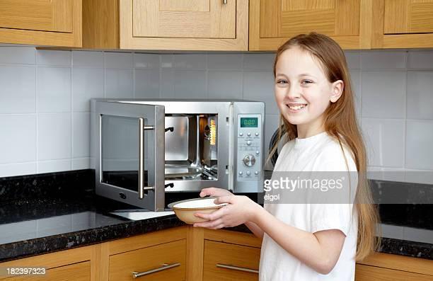 Sorridente ragazza tenendo una ciotola con forno a microonde, facendo Cucina domestica trasformano