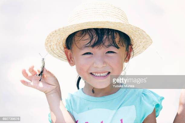 Smiling girl holding butterfly