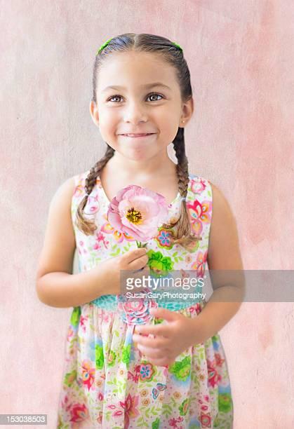 Smiling girl holding pink flower