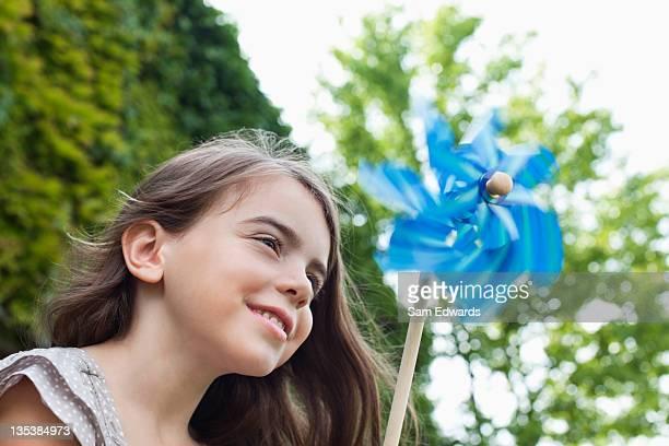 Souriant fille tenant Moulin à vent à l'extérieur