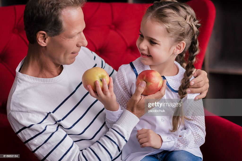 Smiling girl holding two apples with her grandfather : Stock Photo