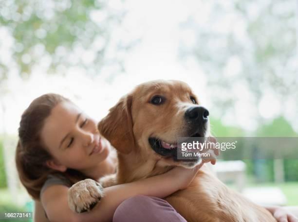 Smiling girl hugging dog outdoors