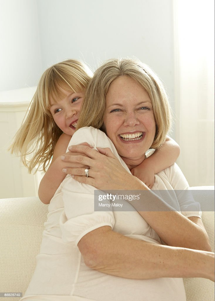 Smiling girl hugging mom from behind. : Stock Photo