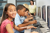 Elementary Students Working At Computers In Classroom Sitting Down Smiling At Camera