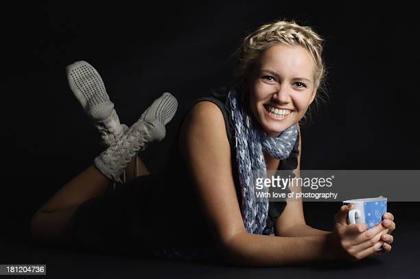 Smiling girl in a scarf, knit socks with cup o tea