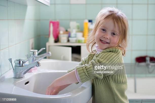 笑顔の女の子のバスルーム、手を洗う