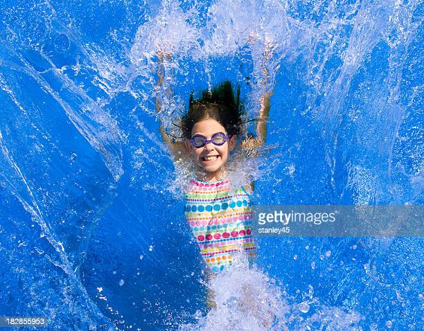 Smiling girl in goggles falling back into a swimming pool